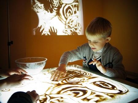 Ребенок рисует песком